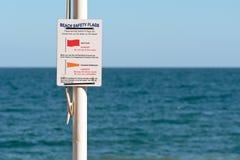 La seguridad de la playa señala la muestra por medio de una bandera en la playa Fotos de archivo libres de regalías