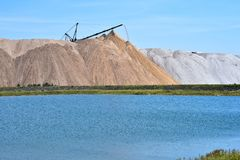 La sel-mine sous forme de colline avec le convoyeur bascule Le premier plan est un étang artificiel photo stock