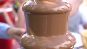 La selección del palillo del pincho de la fruta en la 'fondue' de la fuente del chocolate colocó en una tabla en restaurante del  almacen de metraje de vídeo
