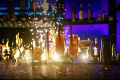 La selezione dei cocktail martini spritz i fuochi d'artificio tonici del fondo del nero della barra del gin della mora Immagine Stock