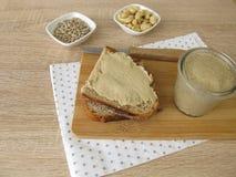 La semilla de girasol del vegano y el anacardo untan con mantequilla en la rebanada de pan Fotos de archivo