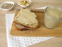 La semilla de girasol del vegano y el anacardo untan con mantequilla en la rebanada de pan Fotografía de archivo libre de regalías
