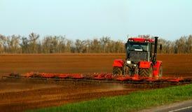 La semina funziona nel campo con un trattore Immagini Stock Libere da Diritti