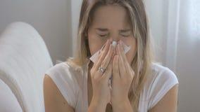 La sensación morena joven de la mujer cogió la gripe que se sentaba en el sofá y que estornudaba en el tejido de papel Cantidad t almacen de metraje de vídeo
