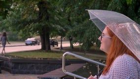 La sensation de la grosse fille de gingembre avec des verres alking vers le haut de petits escaliers en parc par temps pluvieux,  banque de vidéos