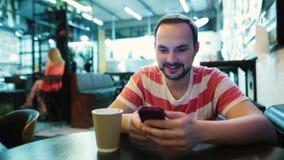La sensibilità barbuta dell'uomo sorpresa o ha colpito quando guarda al suo smartphone stock footage