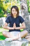 La sentada adolescente asiática relaja la concentración de la yoga Foto de archivo libre de regalías