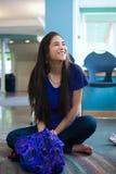La sentada adolescente biracial hermosa de la muchacha cruzó legged en el SMI del piso Foto de archivo