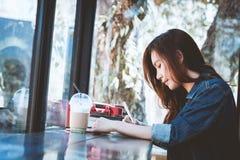 La sentada adolescente de Asia en el pensamiento solamente con hace una nota en café Imágenes de archivo libres de regalías