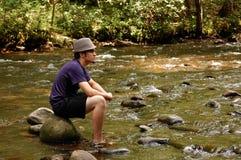 La sentada adolescente en el río oscila, vista lateral Fotografía de archivo