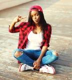La sentada africana joven de la mujer de la moda se está divirtiendo en la ciudad, llevando una gorra de béisbol a cuadros roja d Foto de archivo libre de regalías