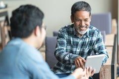 La sentada asiática del hombre de la barba corta vieja feliz, sonriendo y escucha para partner eso que muestra la presentación en imagen de archivo