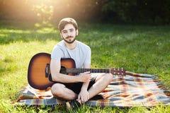 La sentada barbuda relajante del individuo cruzó las piernas en el prado hermoso, guitarra de la tenencia, intentando aprender có Foto de archivo