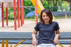 La sentada casual del paño del desgaste adolescente sano asiático relaja sonrisa feliz cuando ejercicio Foto de archivo libre de regalías