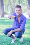 Hombre agachado que señala en usted en parque Imagen de archivo libre de regalías