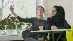 La sentada de dos mujeres hermosas jovenes en el café, uno de ellos mujer musulmán en hijab, tomando el selfie con el teléfono, s almacen de video