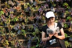 La sentada del adolescente de la mujer del inconformista goza del libro de lectura en el embarcadero Concepto del libro de lectur Foto de archivo libre de regalías