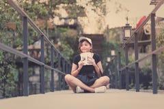 La sentada del adolescente de la mujer del inconformista goza del libro de lectura en el embarcadero Youn Fotos de archivo libres de regalías