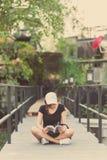 La sentada del adolescente de la mujer del inconformista goza del libro de lectura en el embarcadero Youn Imagenes de archivo