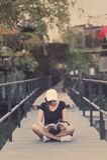 La sentada del adolescente de la mujer del inconformista goza del libro de lectura en el embarcadero Youn Fotos de archivo