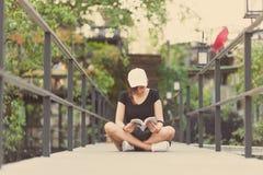 La sentada del adolescente de la mujer del inconformista goza del libro de lectura en el embarcadero Youn Imagen de archivo