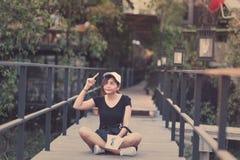 La sentada del adolescente de la mujer del inconformista goza del libro de lectura en el embarcadero Youn Fotografía de archivo libre de regalías