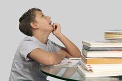 La sentada del muchacho rodeada por los libros y mira soñador para arriba Imagen de archivo