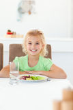 La sentada elegante de la muchacha come su ensalada sana Imagen de archivo libre de regalías