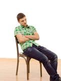La sentada hermosa del hombre joven cayó en una silla Imagen de archivo