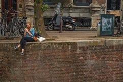 La sentada sola de la chica joven en la pared en los canal's afila, comiendo el helado en Amsterdam Fotos de archivo libres de regalías