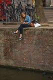 La sentada sola de la chica joven en la pared en los canal's afila, comiendo el helado en Amsterdam Foto de archivo