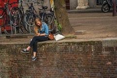La sentada sola de la chica joven en la pared en los canal's afila, comiendo el helado en Amsterdam Fotografía de archivo libre de regalías