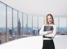 La señora del negocio está sosteniendo una caja negra del documento Oficina panorámica de Nueva York Un concepto de servicios jur Fotografía de archivo