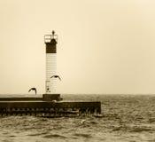 La sepia entonó la imagen del faro en un embarcadero con el silh de los pájaros de vuelo Fotografía de archivo