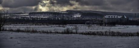 La sera è venuto e le nuvole della forte nevicata stanno venendo da dietro le colline fotografie stock