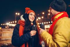 La sera dell'inverno, coppia di amore beve il caffè all'aperto fotografia stock
