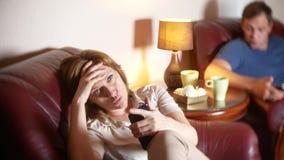 La sera, il marito e la moglie della famiglia si siedono in una sedia nella loro casa e scoprono la relazione immagini stock