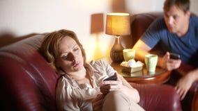 La sera, il marito e la moglie della famiglia si siedono in una sedia nella loro casa e scoprono la relazione fotografia stock