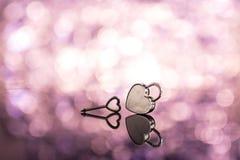 La serratura brillante del cuore del metallo e digita il backgroun rosa del bokeh e della luce Fotografia Stock