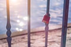 La serratura di amore o il lucchetto di amore davanti ad un lago con la riflessione del sole si svasa Fotografia Stock Libera da Diritti