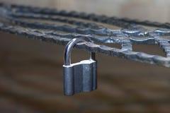 La serrure en métal, s'est verrouillée sur un trellis forgé décoratif en métal photo libre de droits