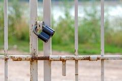 La serrure noire sur la porte avec une serrure contre une herbe verte et la route Photo libre de droits