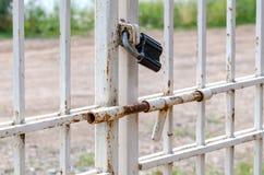 La serrure noire sur la porte avec une serrure contre une herbe verte et la route Photographie stock