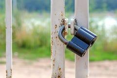 La serrure noire sur la porte contre une herbe verte et la route Photo libre de droits