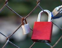 La serrure rouge d'amour a attaché au grillage à côté d'une serrure rouillée Image libre de droits
