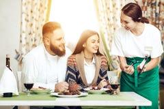 La serveuse a apporté aux couples une facture pour le dîner images stock