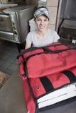 La serveuse avec sortent la pizza dans un sac thermique Photographie stock libre de droits