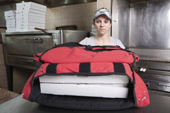 La serveuse avec sortent la pizza dans un sac thermique Photographie stock