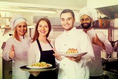 La serveuse et l'équipage du professionnel fait cuire la pose au restaurant Photos libres de droits