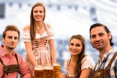 La serveuse livre des bières dans la tente avec les visiteurs heureux dans une tente de bière à Munich Oktoberfest Photographie stock libre de droits